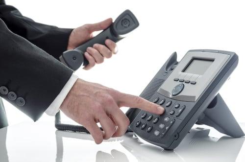Homme en costume composant un numéro de téléphone